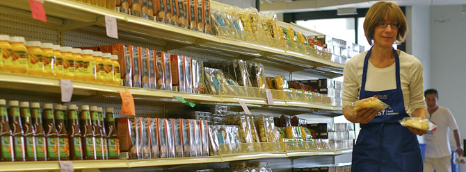 Volunteer stocking shelves at one of our not-for-profit grocery markets.