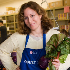 Volunteer displaying some lettuce at one of Quest's grocery markets.