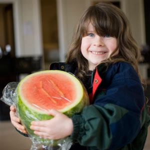 Smiling young girl holding watermelon.